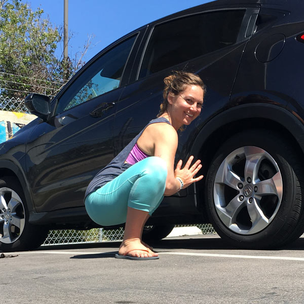 Yoga frog pose next to a car