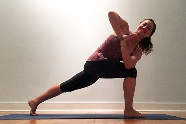 Yoga teacher in revolved lunge pose