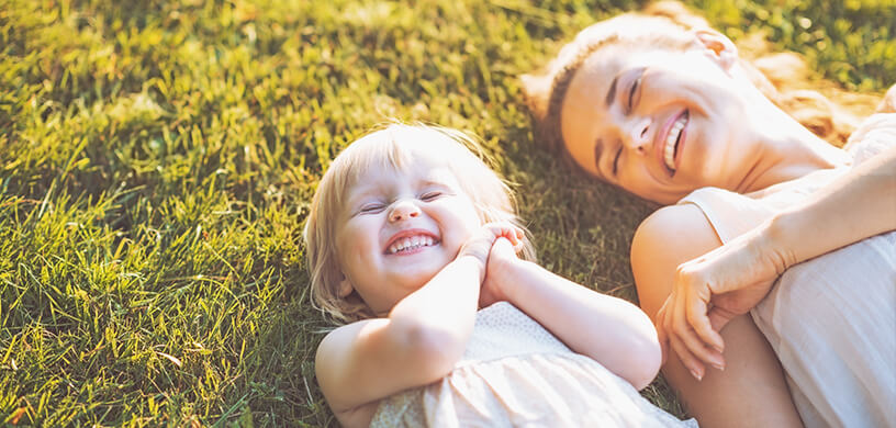 woman and child laughing in lawn