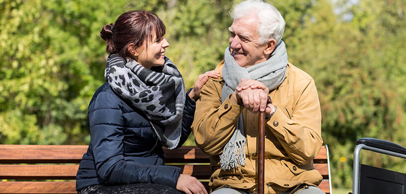 caretaker enjoying afternoon on bench with older gentleman