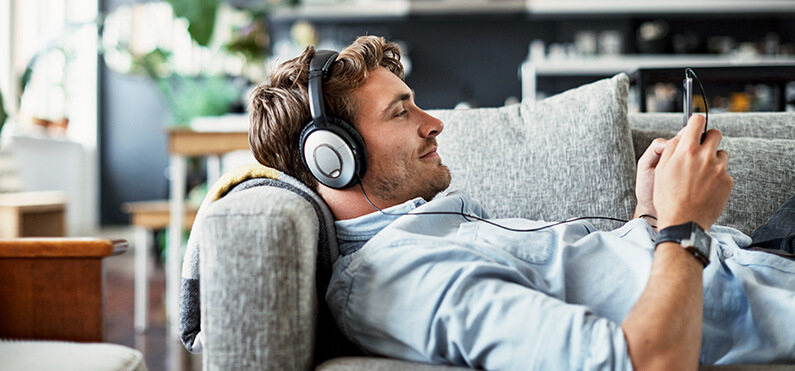 man listening to podcast on couch