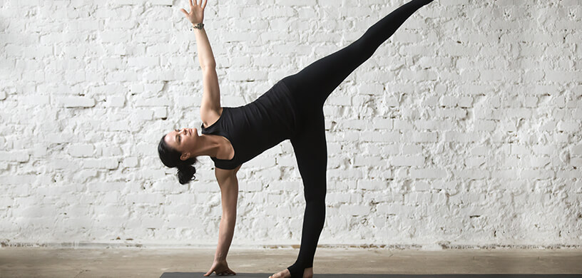 woman doing yoga half moon pose