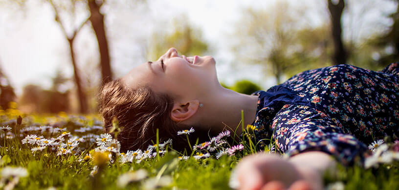 happy woman laying in grass