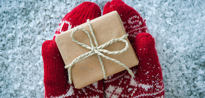hands in mittens holding gift box