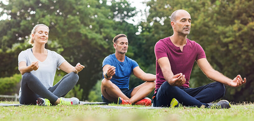 group meditating outdoors