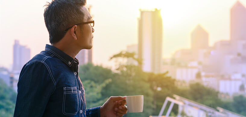 man drinking coffee looking outside