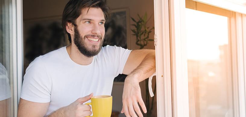 man smiling in the morning drinking tea