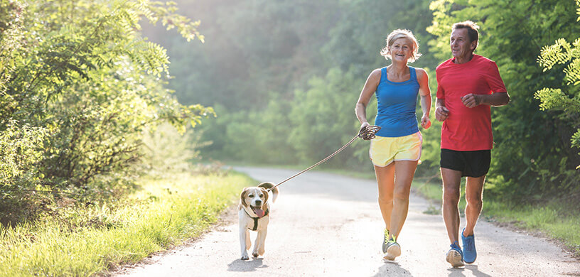 mature man and woman running with their dog