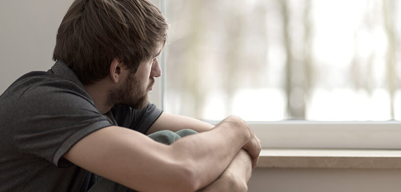 sad young man looking outside the window