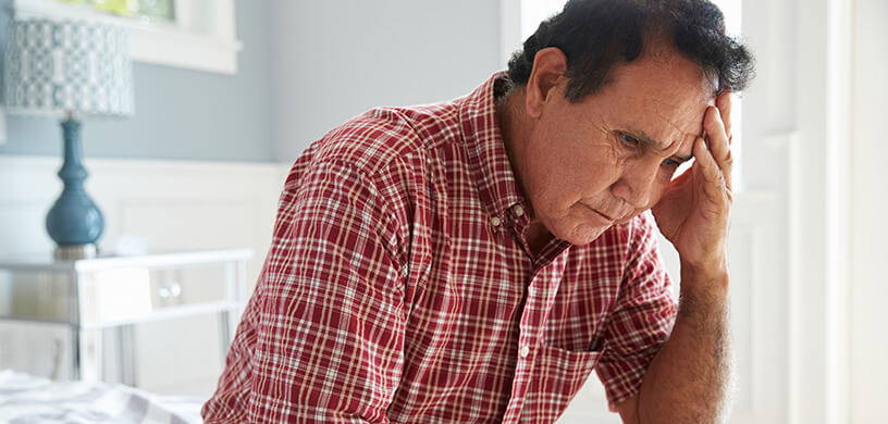 Senior hispanic man sitting on bed in thought
