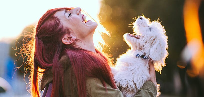 woman laughing with her dog