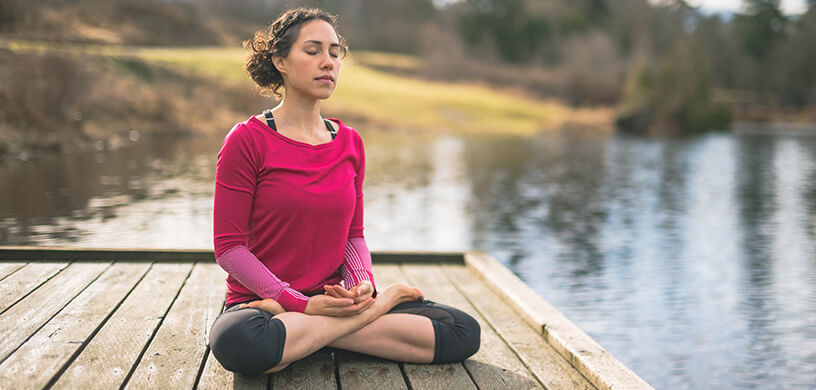 woman meditating at lake