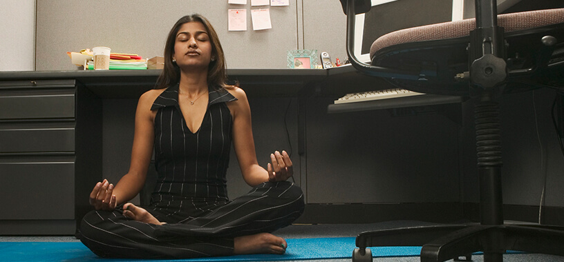 Woman Meditating On The Floor At Work