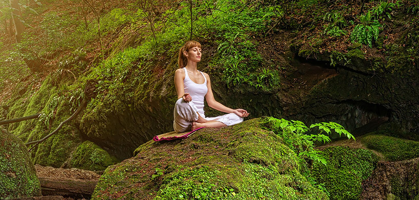 A woman meditating in lotus pose in the forest