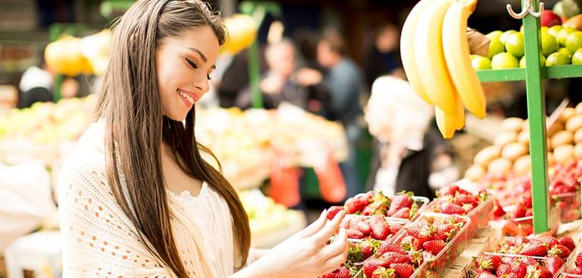 A young woman shopping for strawberries at a farmers market
