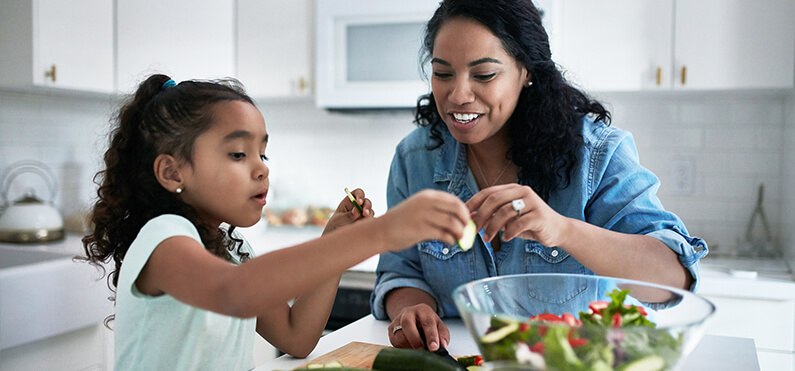 mom and daughter prepping food
