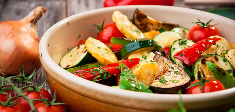 bowl full of roasted zucchini, bell peppers, and tomatoes