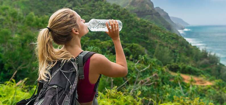 travelling girl drinking water hiking