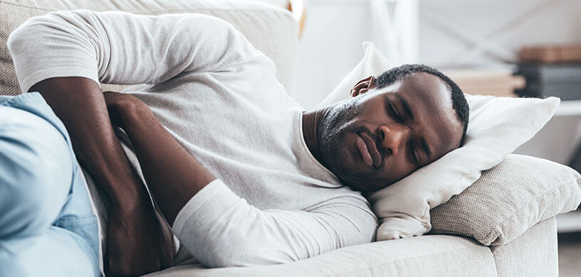 man on couch suffering stomach pain