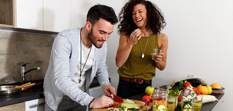 A couple cooking a healthy vegetable meal at home