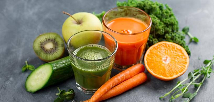 Fresh squeezed green and orange juices with fruits and vegetables