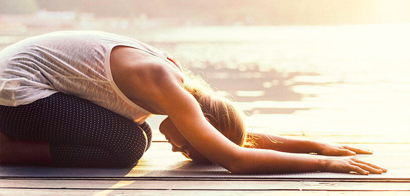 woman in childs pose on yoga mat