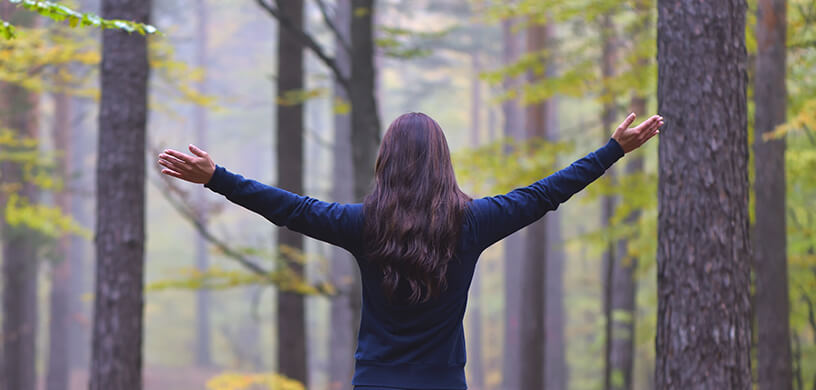 woman with arms open in forest
