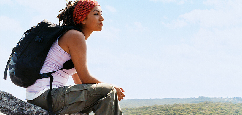 woman contemplating sitting on rock hiking