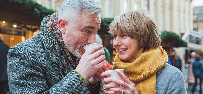 mature couple giggling drinking hot cocoa