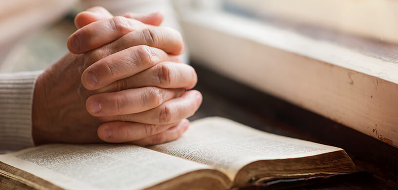 Man holding hands in prayer over a book