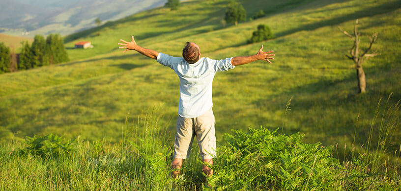 Man standing on a mountain top with raised arms