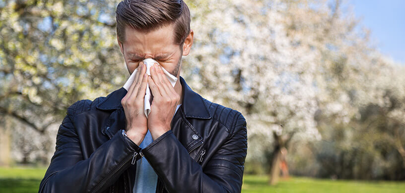 A man suffering from an allergy in the spring