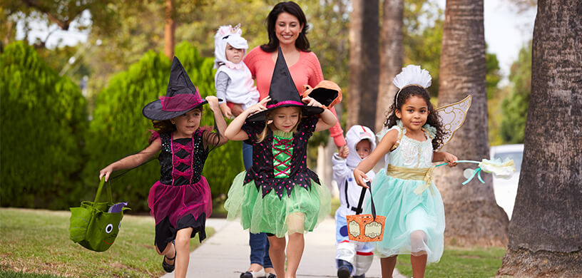 Mom and kids dressed up for Halloween with bags for candy