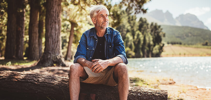 mature man outdoors camping by lake