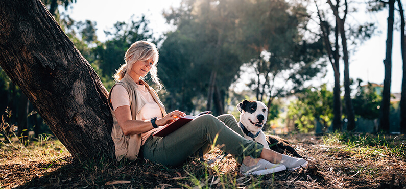 woman enjoying nature journaling with pet