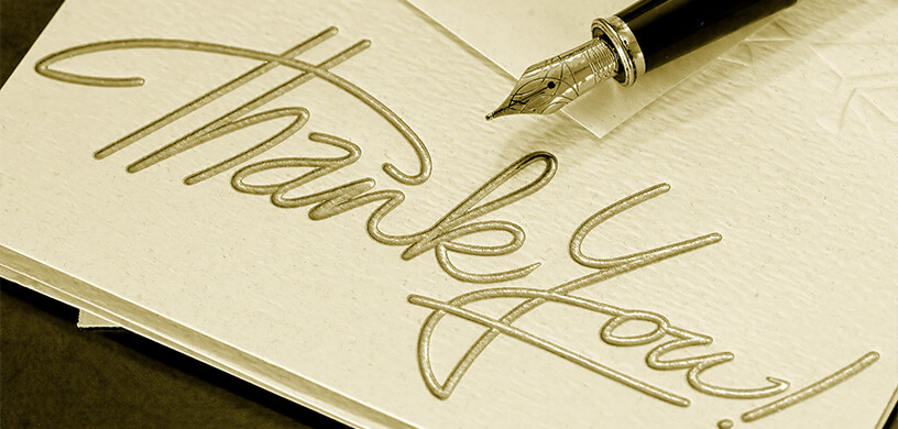 A thank you card with a pen and envelope