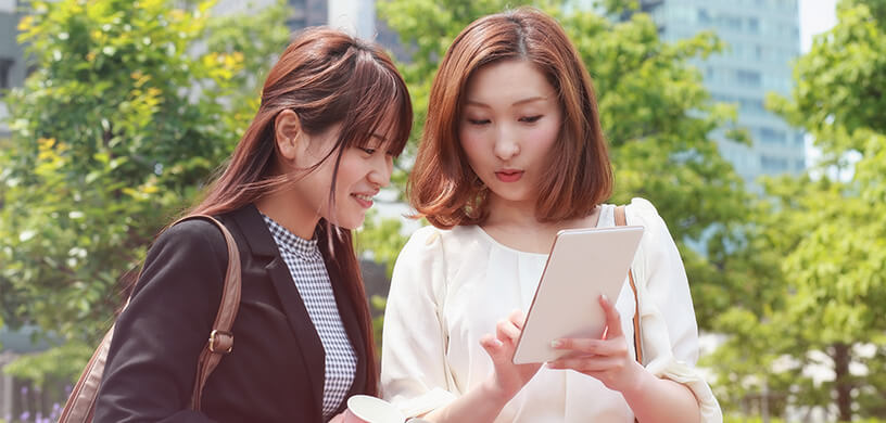 Two young women looking at an electronic tablet