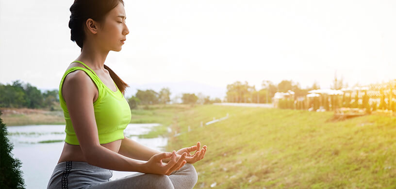 athletic woman meditating outdoors