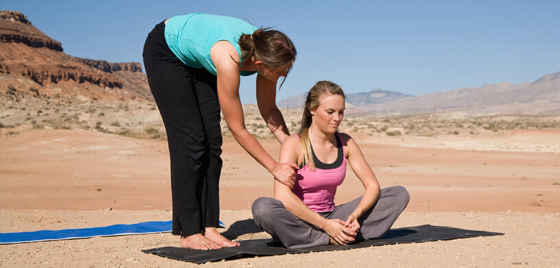 woman teaching yoga in desert