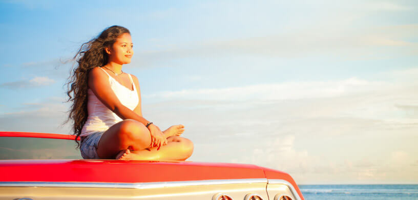 A young woman doing yoga on a road trip