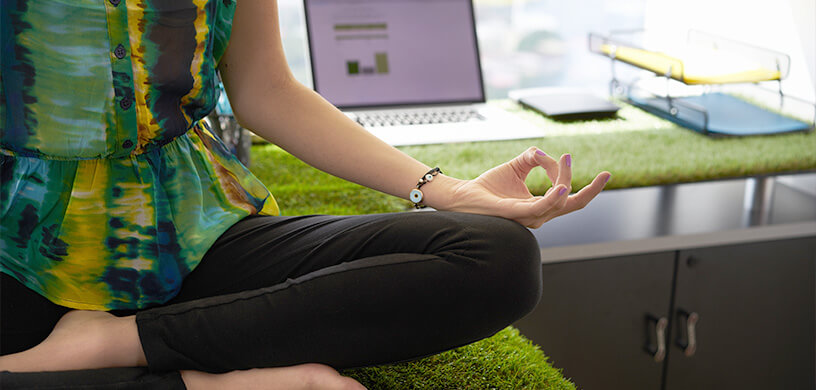 Woman sitting in meditation on a desk at the office