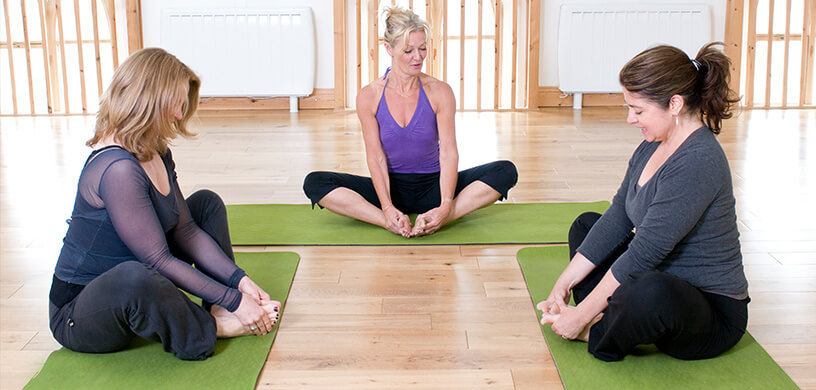 A yoga teacher with two female yoga students