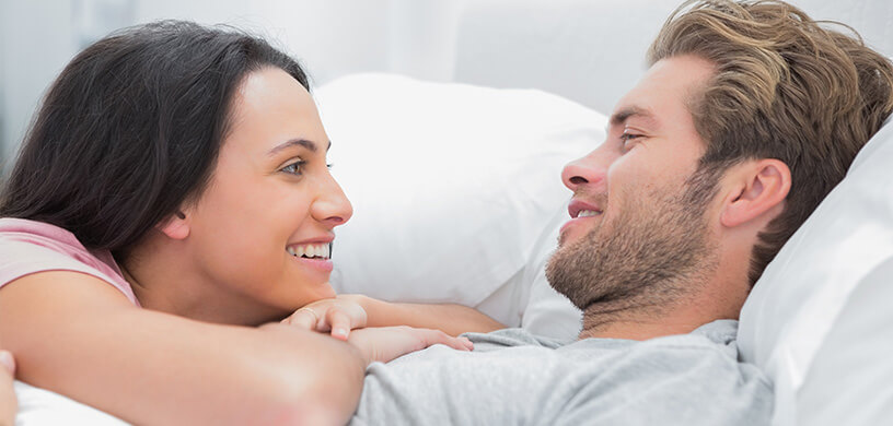 A young couple laying in bed looking into each other's eyes
