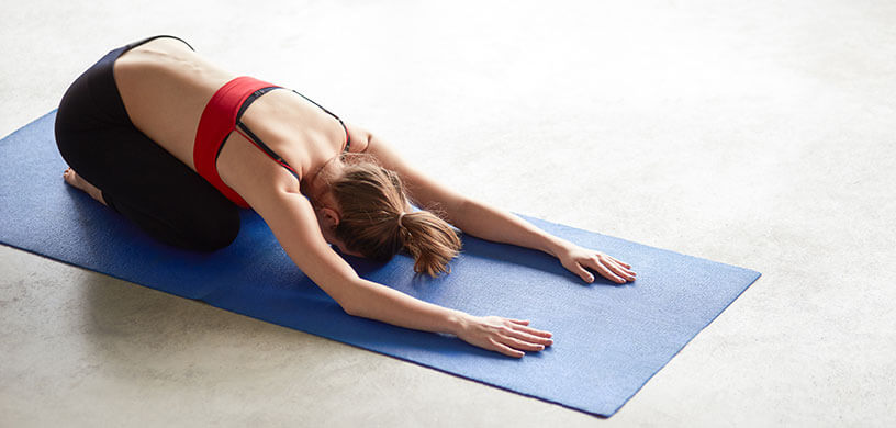 Young teacher laying on yoga mat in child's pose