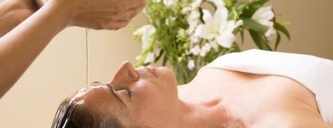 Woman receiving a shirodhara ayurvedic treatment