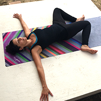 Woman in yoga supine spinal twist pose
