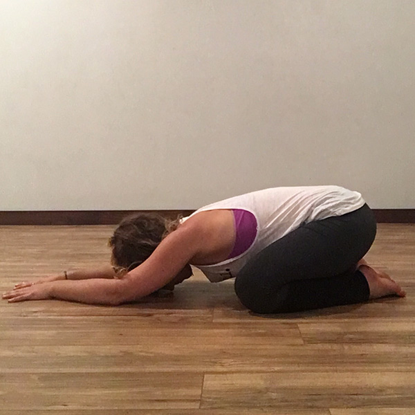 A young woman in child's yoga pose