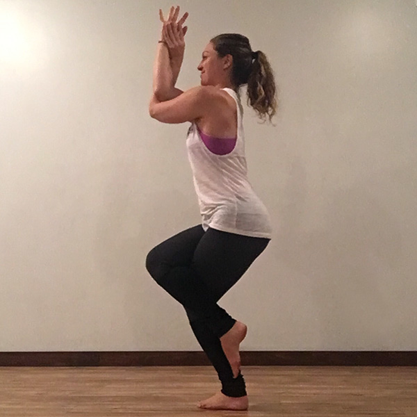 A young woman in eagle yoga pose